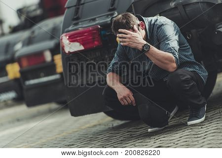 Caucasian Trucker with Problems. Devastated Men and His Fleet of Trucks. Business Owner Facing Bankruptcy.