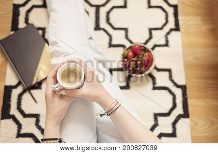 A Young Woman Wearing Distressed Jeans Sitting On Wood Floor On A Rug Carpet At Home And Holding A C