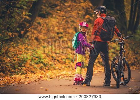Family Outdoor Activities. Father and Daughter in the Park. Biking and Roller Skates.