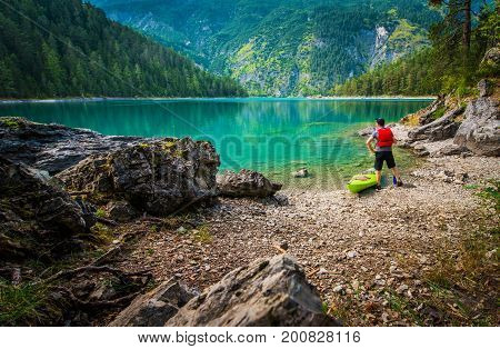 Scenic Lake Kayak Tour. Caucasian Men Enjoying the View From the Lake Shore. Tyrol Austria.