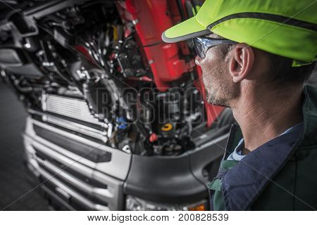 Semi Trucks Caucasian Mechanic Preparing For The Job. Truck Maintenance Concept Photo.