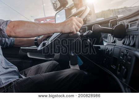 Semi Truck Driving Job. Caucasian Men Behind Semi Truck Steering Wheel. Cabin Interior. Transportation and Spedition Industry.