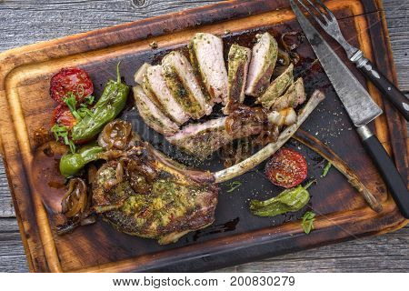 Barbecue tomahawk pork steak with vegetable and onion as top view on a cutting board