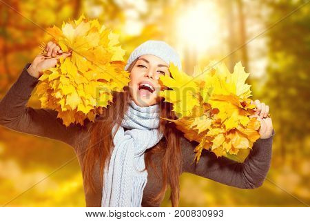 Beautiful Happy Autumn girl holding bunches of bright yellow autumn leaves and laughing. Beauty fall sunny park. Beautiful young woman wearing knitted blue scarf and a hat. Autumn fashion
