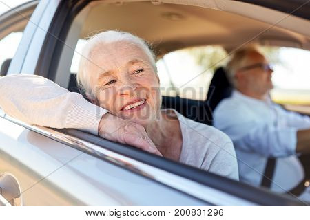 road trip, travel and old people concept - happy senior couple driving in car