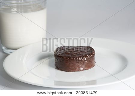 Chocolate ding dong on plate with a glass of milk