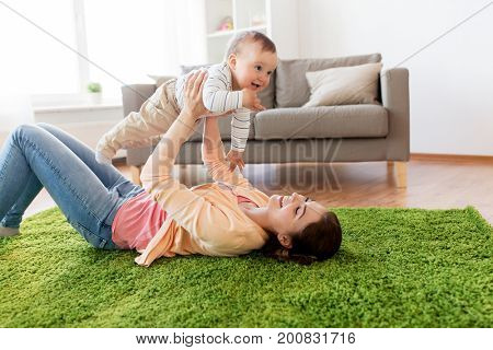family, child and motherhood concept - happy smiling young mother playing with little baby at home