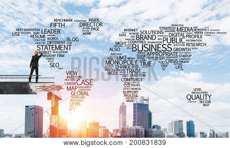 Businessman in helmet writing business-related terms in form of world map while standing on broken bridge with cityscape and sunlight on background. 3D rendering.