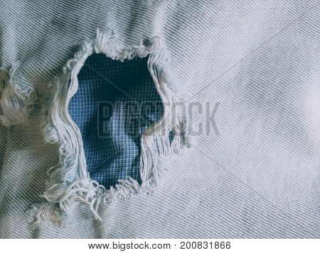 Hole in denim fabric close-up