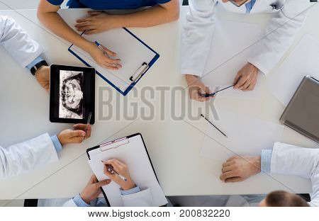 medicine, healthcare and oral surgery concept - group of doctors or surgeons discussing jaw x-ray on tablet pc computer screen at hospital or face and jaw surgery center