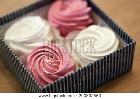 food, confection and sweets concept - close up of zephyr, marshmallow or whipped cream in gift box on wooden table