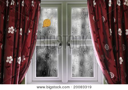 Rain on a window with curtains