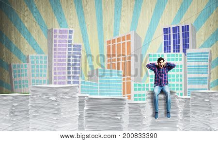 Attractive man in casual clothing sitting on pile of documents with sketched cityscape view on background. Mixed media.