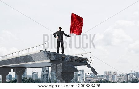 Rear view of confident businessman in suit holding red flag in hand while standing on broken bridge with cityscape on background. 3D rendering.