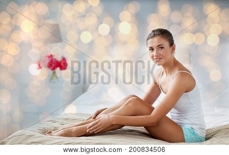 people, beauty, depilation, epilation and bodycare concept - beautiful woman touching smooth leg skin on bed at home bedroom