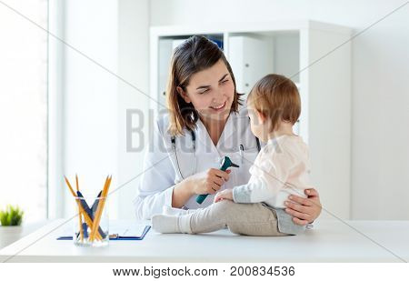 medicine, healthcare, pediatry and people concept - otolaryngologist or doctor with baby and otoscope at clinic