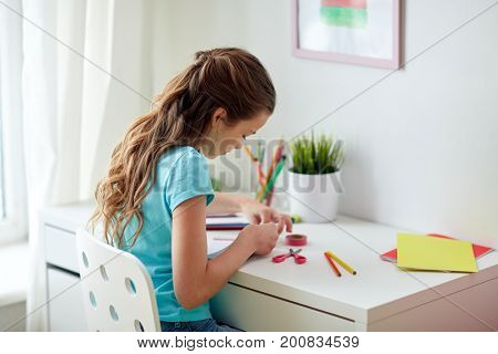 people, children, creativity and art concept - happy girl making something at home