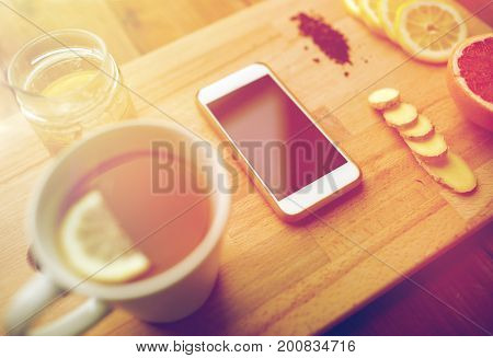 health, traditional medicine, folk remedy and ethnoscience concept - smartphone with cup of ginger tea, honey and citrus on wooden board