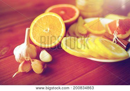 health, traditional medicine and ethnoscience concept - garlic, lemon, orange and other folk remedy on wooden background