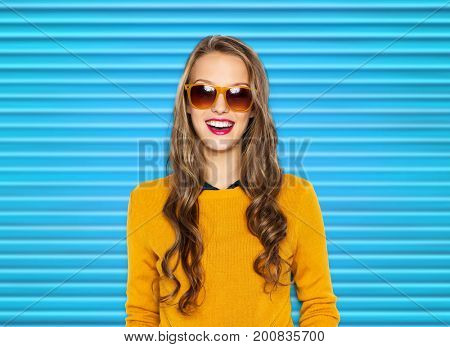 people, summer and fashion concept - happy young woman or teen girl in casual clothes and sunglasses over blue ribbed background