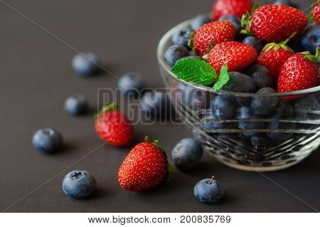 top view of Strawberry and blueberry in glass bowl on round plate mat, selective focus of mix fresh fruit