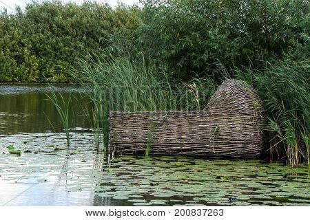 floating wooden cradle basket in water with lily pads in Kinderdijk the Netherlands