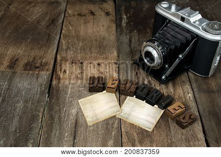 old camera with blank snapshot frames on rustic wood and letterpress type sign