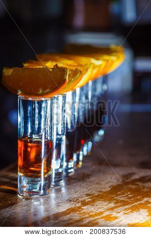 A number of shots with golden tequila and orange slices. Close-up