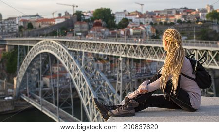 Young female sitting on the top observation deck on the Douro river, overlooking the bridge Dom Luis I, Porto, Portugal.