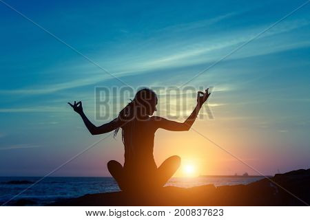 Yoga and healthy lifestyle background, silhouette of woman meditating on the sea beach.