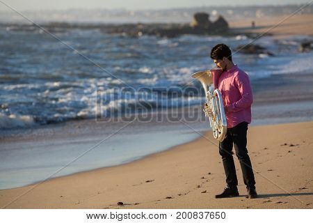 Musician with musical instrument Tuba on romantic sea shore.