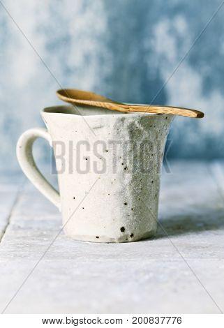 Ceramic mug and wooden tea spoon