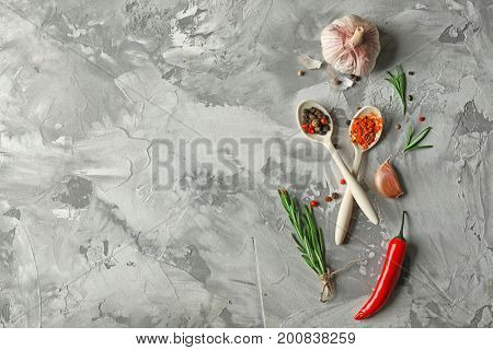 Composition with fresh rosemary and spices on grey background