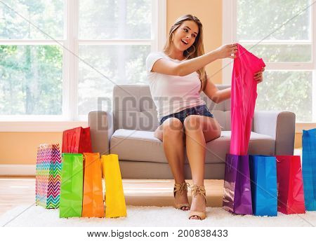 Young woman with many brightly colored shopping bags in her living room