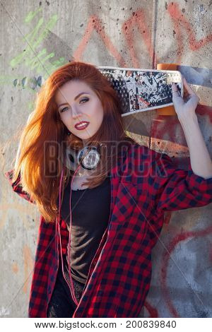 Beautiful young girl with  skateboard in the city in sunny weather
