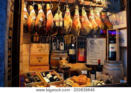 Siena Italy,October 26th 2013.A shop window in Siena Italy displays its wares in the window of its shop.Step inside and but some fine Tuscan wine,prosciutto and bread.Come explore Siena Tuscany