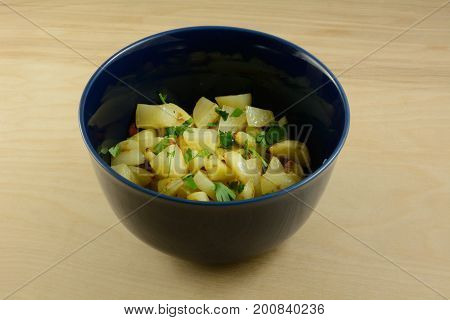Homemade low calorie potato and carrot salad side dish in blue bowl on wooden table