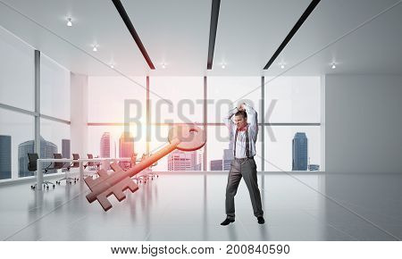 Determined businessman in modern interior breaking with hands stone key figure