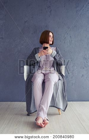 Vertical of nice girl postponing using smartphone and sitting on armchair with copy space