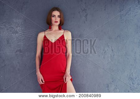 Wide shot of professional model posing in red dress on grey background with copy space
