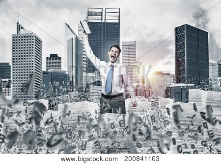 Businessman keeping hand with book up while standing among flying letters with cityscape and sunlight on background. Mixed media.