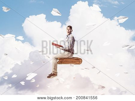 Young man in casual sitting on old book with one in hands