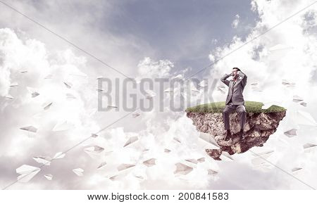 Frustrated businessman sitting on green island and closing ears with hands