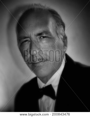Portrait of an older white man in formal dress tuxedo slicked back hair and pencil mustache looking at viewer with black and white old hollywood finish.