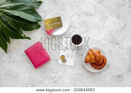 Paying at cafe by card. Bill and coins near coffee, croissant and wallet on light stone table top view.