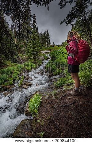 Hiking Colorado Girl Backpacker Looks At Cascading Creek Near Lake Isabelle