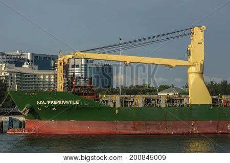 Labuan,Malaysia-July 23,2017: A large cargo ship with ship cranes in the port of Labuan island,Malaysia.The abolishment of cabotage policy is set to benefit this duty-free-island economically