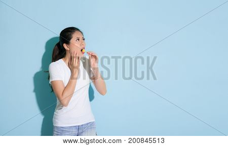 Attractive Female Student Standing On Blue Wall