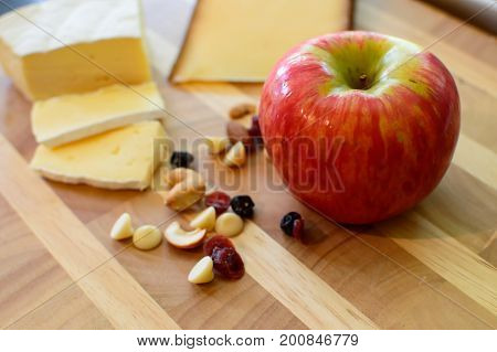 Apple and cheese plate, Healthy snack choices, apple and dried fruit and nuts on wood background with gouda cheese, smoked gouda, brie cheese, sliced cheeses and fresh cashew nuts, dried cranberry fruit, yogurt chips, dried blue berry and oji berry next t