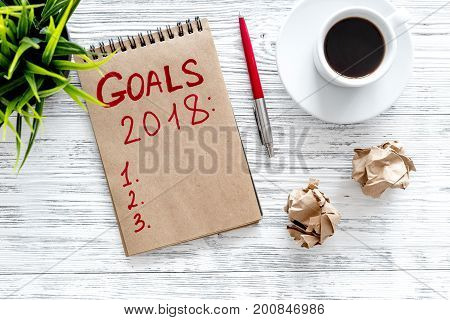 Make a goals list for 2018. Notebook near pen and cup of coffee on grey wooden background top view.